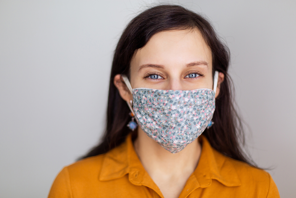 dark haired woman wearing a floral face mask