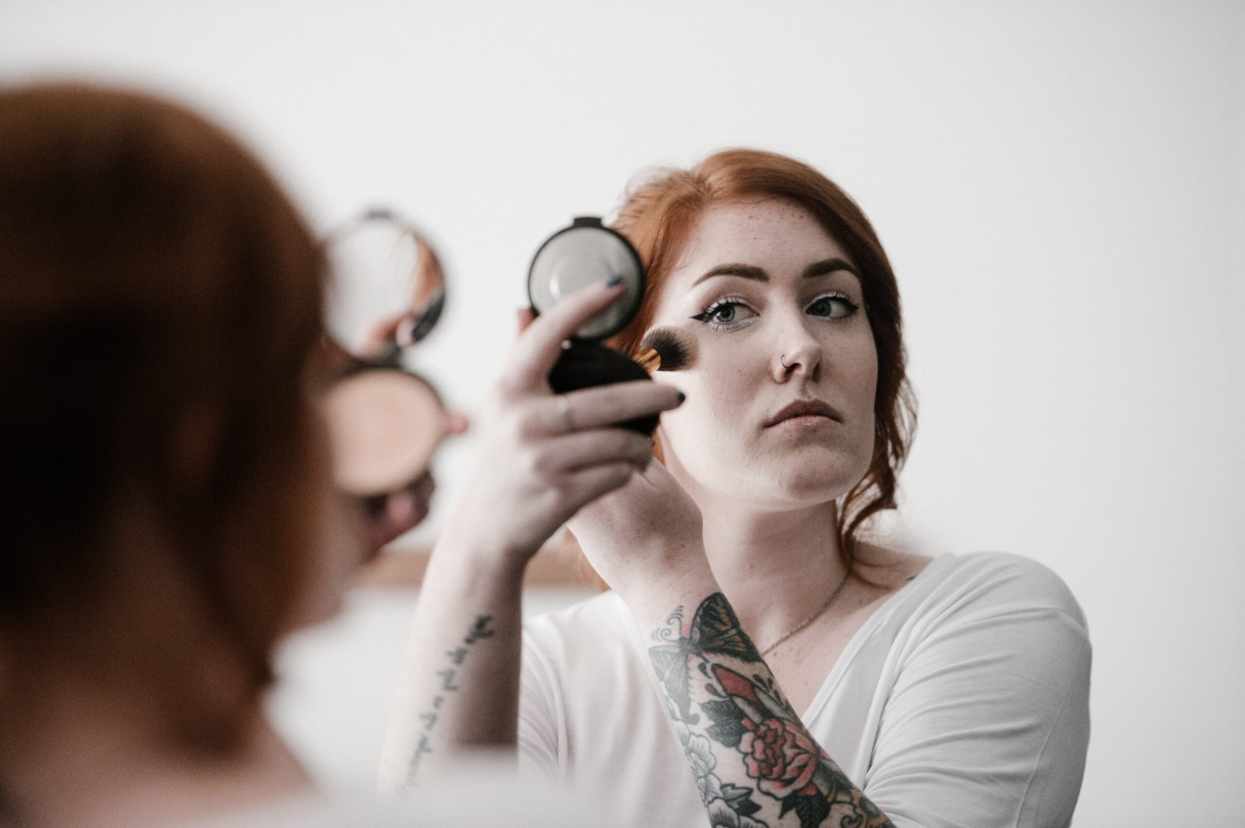 woman applying makeup to her face