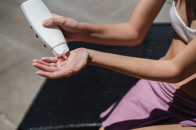 Woman squeezing sunscreen into her hand